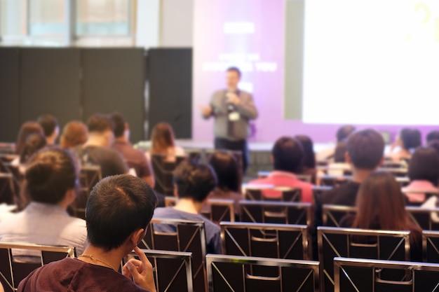 Conférencier à l'écoute du public qui se tient devant la salle dans la salle de conférence Photo Premium