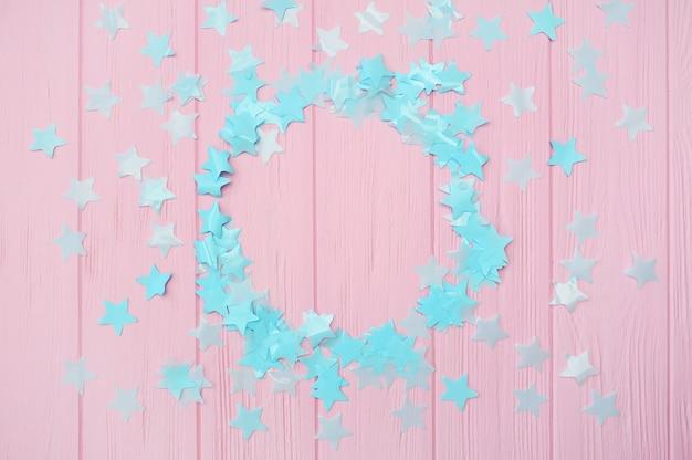 Confetti d'étoiles bleues sur fond en bois rose avec cadre rond Photo Premium