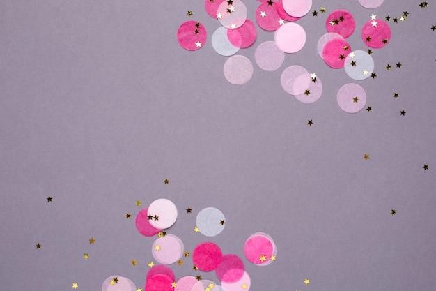 Confetti rose avec des étoiles d'or sur gris Photo Premium