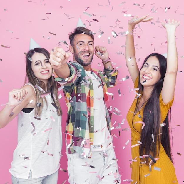 Confettis d'argent tombant sur les amis dansant sur fond rose Photo gratuit