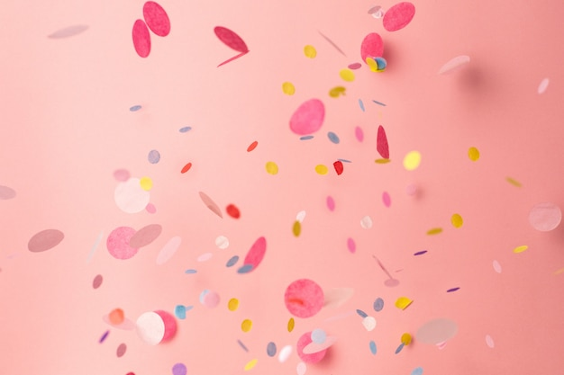 Confettis colorés sur fond rose pastel Photo Premium
