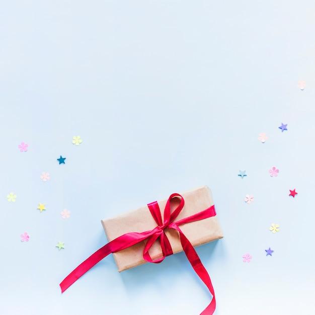 Confettis couché près du présent Photo gratuit