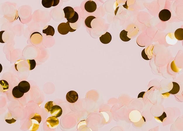 Confettis à la fête du nouvel an avec fond rose Photo gratuit