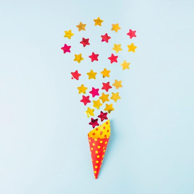 Confettis de forme d'étoile sur le cône de papier sur fond bleu Photo gratuit