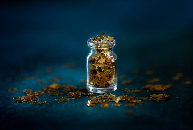 Confettis De Paillettes D'or Dans La Petite Bouteille En Verre Photo Premium