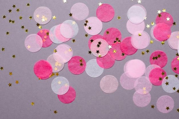 Confettis roses avec des étoiles d'or sur gris avec fond Photo Premium