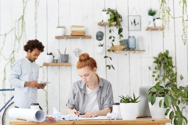 Confiant Ingénieur Femme Qualifiée Faisant Des Croquis à L'aide D'un Stylo Et De Matériel D'ingénierie Photo gratuit