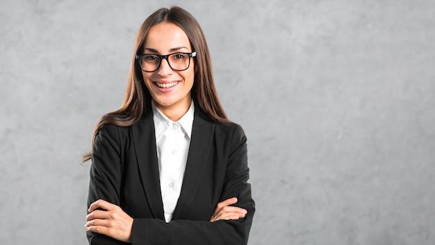 Confiant jeune femme debout contre le mur gris Photo gratuit