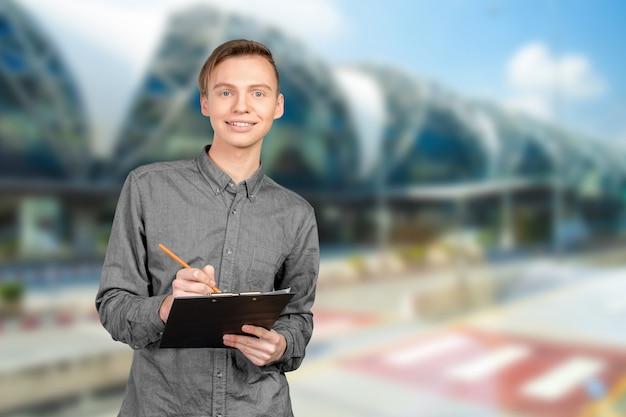 Confiant jeune homme en chemise prendre des notes dans son carnet Photo Premium