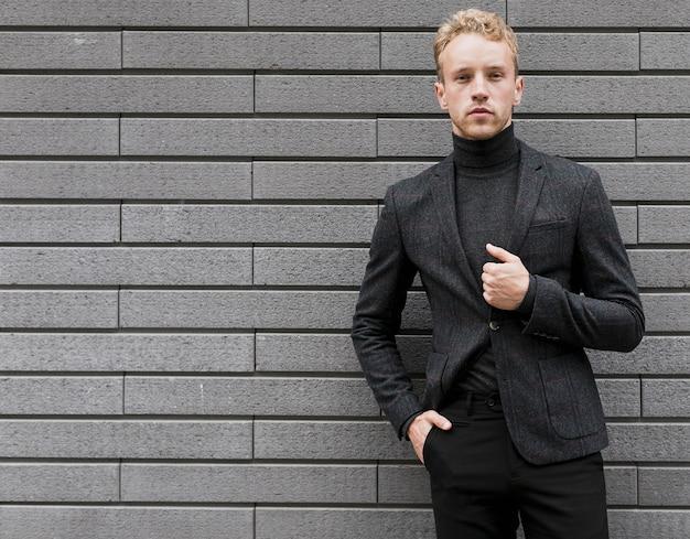 Confiant jeune homme avec sa main dans la poche sur fond gris Photo gratuit