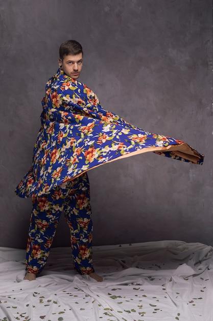 Confiant jeune homme soufflant son drapé floral contre le mur gris Photo gratuit