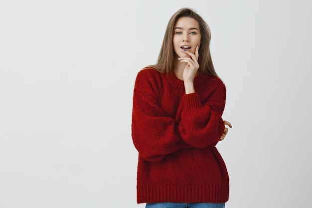 Confiante Belle Femme Européenne Sexy Impertinente En Pull Lâche Rouge Mordant Le Doigt à La Recherche D'audace Et De Séduction, Sûre D'elle-même Avec Un Regard Sensuel Sur Photo gratuit
