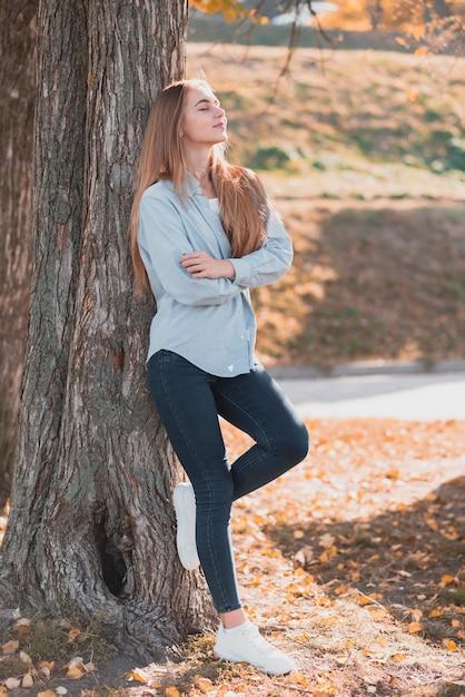 Confiante femme blonde posée sur un arbre Photo gratuit