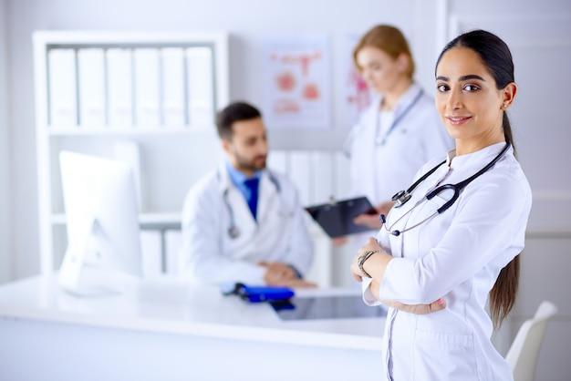 Confiante Femme Médecin En Face De L'équipe, à La Recherche D'une équipe Multiraciale Souriante Avec Une Femme Médecin Arabe Photo Premium