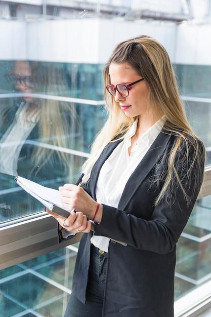 Confiante jeune femme blonde écrit dans le document avec un stylo Photo gratuit