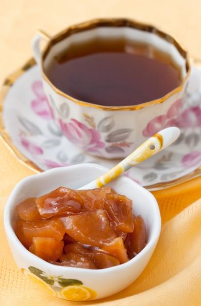 Confiture de coings hommade et tasse de thé sur fond jaune Photo Premium
