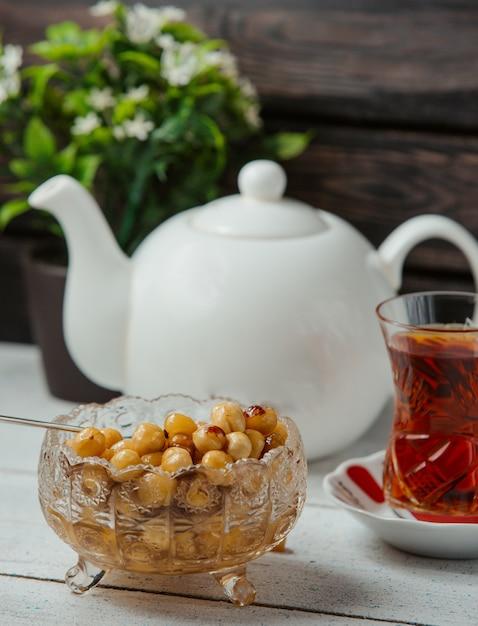 Confiture de noisettes azerbaïdjanaise dans un bol en cristal avec thé noir Photo gratuit
