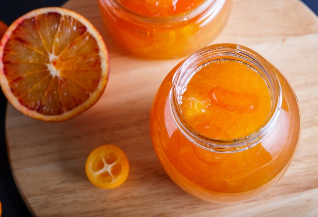 Confiture d'orange et de kumquat dans un bocal en verre avec des fruits frais sur un plateau de cuisine en bois. Photo Premium