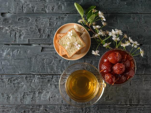 Confiture de pomme, thé, pain et un brin de fleurs de cerisier sur une table sombre. Photo Premium