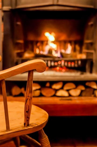 Confort à la maison. chaise à bascule près de la cheminée. photo de l'intérieur de la pièce. chaise à bascule dans le salon avec cheminée moderne décorée Photo gratuit