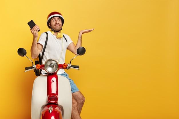 Confus Beau Conducteur Masculin Sur Scooter Avec Casque Rouge Photo gratuit