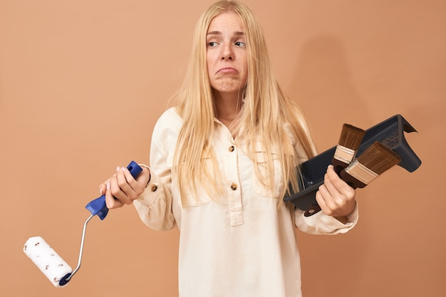 Confus Jeune Femme Aux Longs Cheveux Raides Posant Sur Un Espace Copie Vierge Tenant Des Outils Spéciaux Tout En Peignant Les Murs Photo gratuit