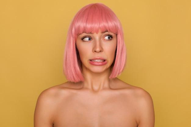 Confus Jeune Jolie Femme Aux Cheveux Roses Aux Yeux Bleus Avec Coupe De Cheveux Bob Montrant Ses Dents Tout En Tordant Avec Embarras Sa Bouche, Isolée Sur Un Mur De Moutarde Photo gratuit