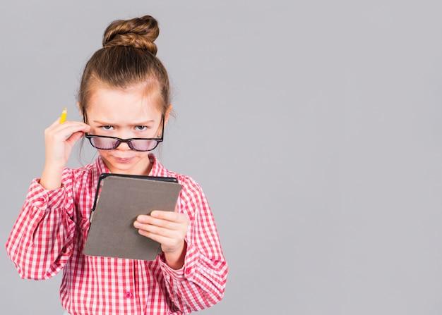 Confus petite fille à lunettes à l'aide de tablette Photo gratuit