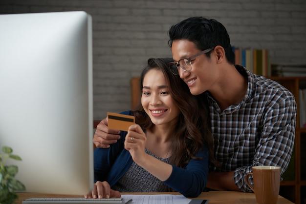 Les conjoints effectuant un paiement avec une commande par carte de crédit dans une boutique en ligne Photo gratuit