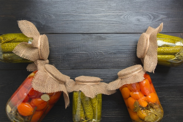 Conserves de légumes concombre et tomate dans des bocaux en verre sur un tableau noir woodeb. vue d'en-haut. différents types de conserves. devoirs et traditions. Photo Premium