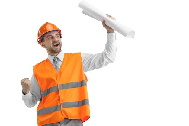 Le Constructeur Dans Un Gilet De Construction Et Un Casque Orange Debout Sur Un Mur Blanc. Spécialiste De La Sécurité, Ingénieur, Industrie, Architecture, Gestionnaire, Profession, Homme D'affaires, Concept D'emploi Photo gratuit