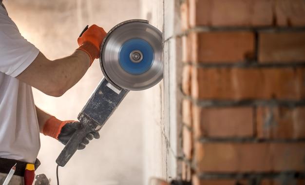 Le Constructeur Industriel Travaille Avec Une Meuleuse D'angle Professionnelle Pour Couper Des Briques Et Construire Des Murs Intérieurs. électricien. Photo gratuit