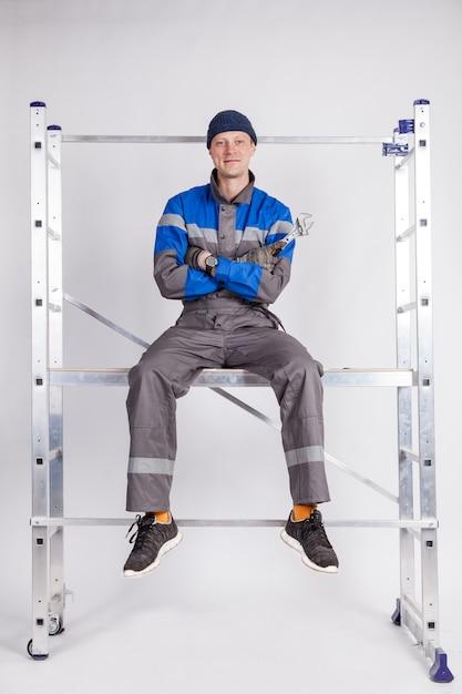 Le constructeur, l'installateur est assis en hauteur, un outil à la main Photo Premium