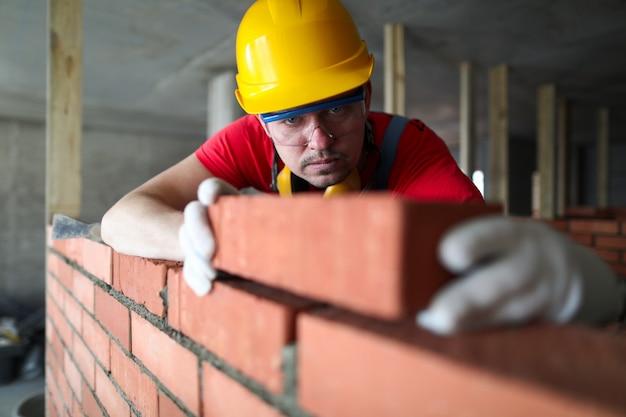 Le Constructeur Met Soigneusement La Brique Rouge Sur La Maçonnerie Photo Premium