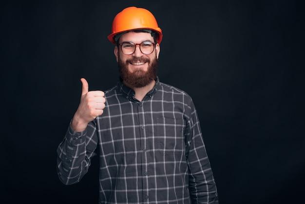 Un Constructeur Montre Un Pouce Levé Et Sourit à La Caméra Près D'un Mur Noir. Photo Premium