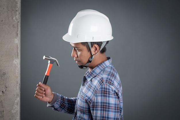 Le constructeur tient un marteau sur le mur de plâtre sur un fond gris Photo gratuit