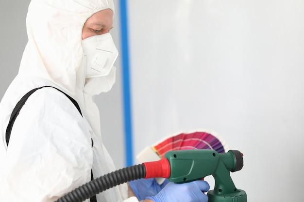 Le Constructeur En Uniforme Choisit La Couleur Pour Peindre Le Mur Photo Premium