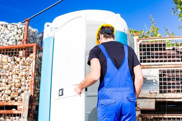 Constructeur utilisant des toilettes mobiles sur place Photo Premium