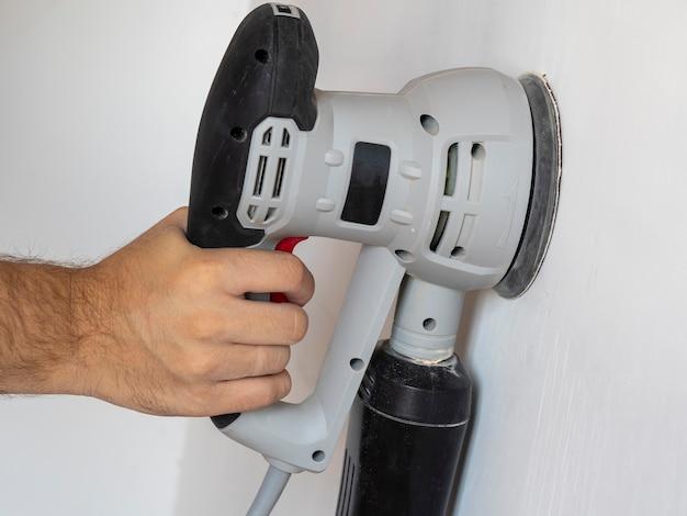 Un Constructeur Utilise Une Ponceuse Pour Traiter Un Mur De Béton Blanc. Concert De Construction Photo Premium