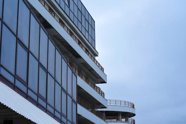 La construction d'un bâtiment moderne avec un parking en verre et de longs balcons Photo Premium