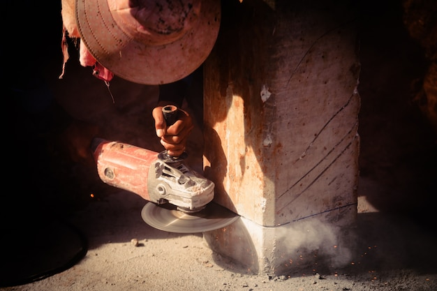 Construction homme ouvrier tenant une scie électrique couper le béton Photo Premium