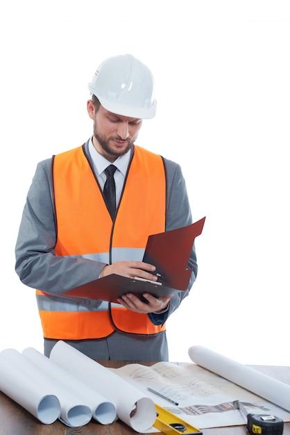 Constructionist portant gilet de sécurité et casque prenant des notes sur son presse-papiers isolé sur blanc. Photo Premium