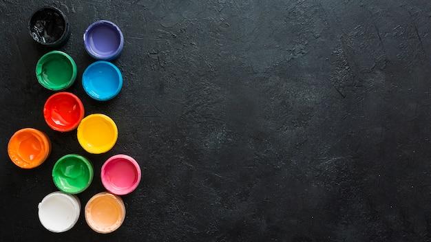 Contenants De Peintures Colorées Sur Fond Texturé Noir Photo gratuit