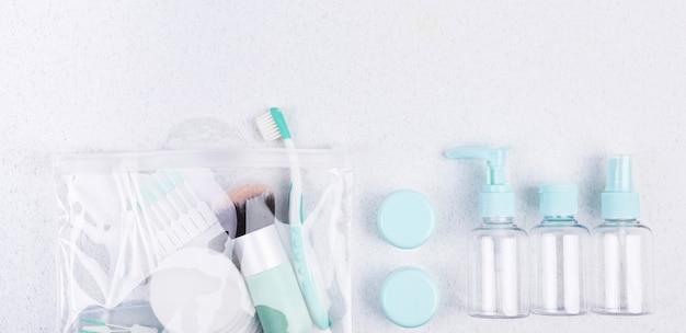 Contenants en plastique, brosse à dents et pinceau de maquillage. set de voyage flat lay Photo Premium