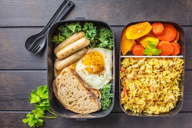 Contenants de préparation de repas avec du riz avec du poulet, des légumes cuits au four, des œufs, des saucisses et de la salade. Photo Premium