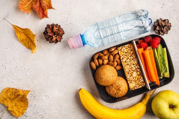 Contenants de préparation de repas sains à l'école avec barre de céréales, fruits, légumes et collations. plats à emporter sur fond blanc, vue de dessus. Photo Premium