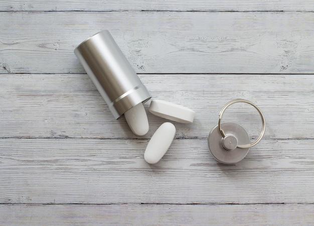 Conteneur en métal et pilules sur un fond en bois Photo Premium