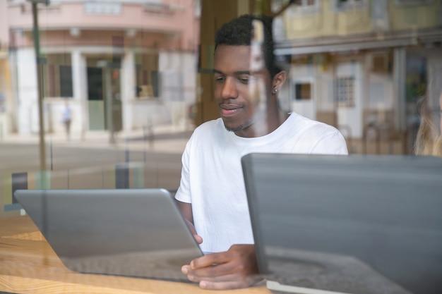 Content African American Guy Assis à Table Et Utilisant Un Ordinateur Portable Photo gratuit
