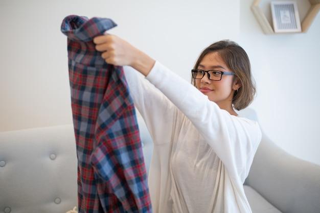 Contenu asiatique jeune femme soulevant la chemise à la maison Photo gratuit
