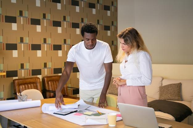Contenu Concepteur Afro-américain Expliquant Le Projet Au Client Et Montrant Le Brouillon Photo gratuit